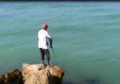 Pesca in Oman Sud da riva, foto di uno spot sulle coste nel Dhofar, intorno a Salalah nel Mar Arabico, parte dell' Oceano Indiano. Recupero dell' artificiale a spinning.