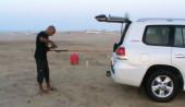 Pesca in Oman Sud dalla spiaggia, foto di uno spot sulle coste nel Dhofar, intorno a Salalah nel Mar Arabico, parte dell' Oceano Indiano. Preparazione della attrezzatura da pesca a spinning.