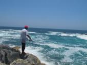 Pesca in Oman Sud dalla costa, foto di uno spot sulle coste nel Dhofar, intorno a Salalah nel Mar Arabico, parte dell' Oceano Indiano. Il pescatore sta effettuando la pesca a spinning.